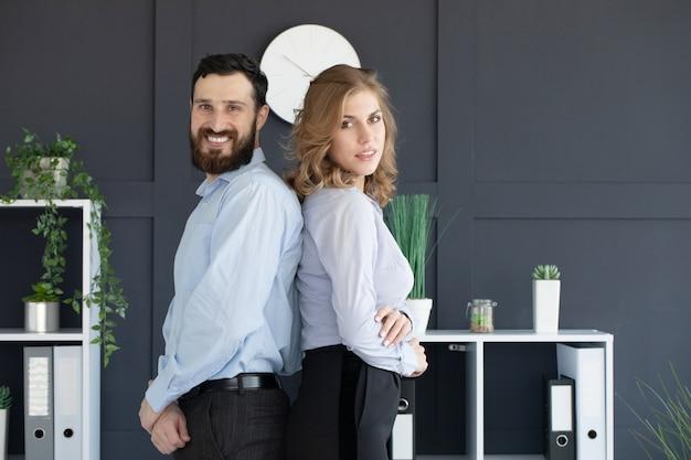 Succesvolle zakenpartners met een jonge man en vrouw die rug aan rug poseren.