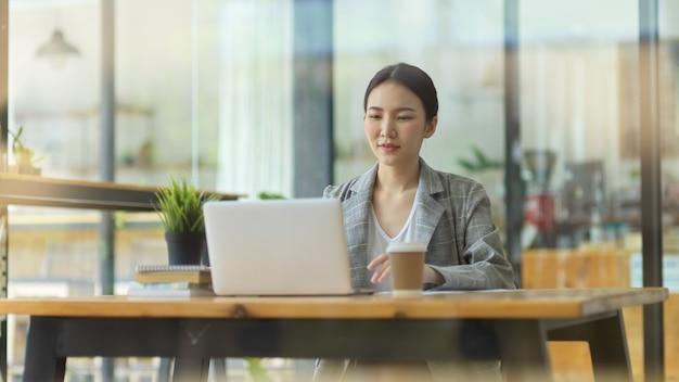 Succesvolle zakenvrouw die tijdens de lunchpauze op een laptop in een café werkt en een zakelijk project beheert