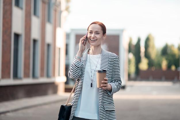 Succesvolle zakenvrouw. glimlachende succesvolle jonge zakenvrouw in trendy accessoires die een papieren kopje koffie draagt terwijl ze buiten telefoneert