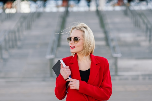 Succesvolle zakenvrouw in rode jas praten over smartphone onderhandelen over een deal op de achtergrond van hoge gebouwen in het business center.