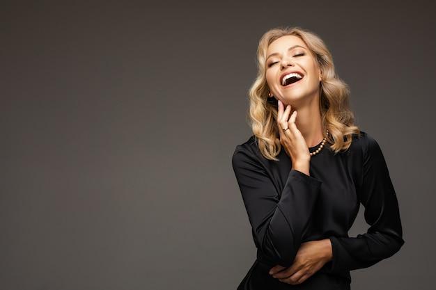 Succesvolle zakenvrouw in zwarte jurk met kralen op nek lachen met gesloten ogen hand in hand op haar nek. kopieer ruimte.
