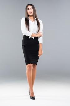 Succesvolle zakenvrouw met armen gekruist op wit. mooie bedrijfsvrouw. volledig lengtebeeld van jonge onderneemster.