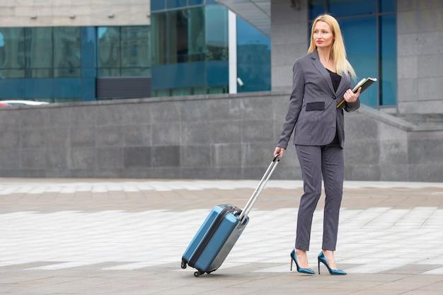 Succesvolle zakenvrouw met reiskoffer met documenten in de hand op stadsstraat