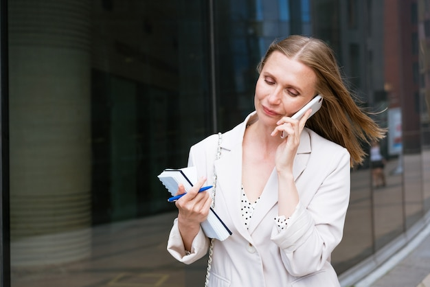 Succesvolle zakenvrouw of zakenvrouw die aantekeningen maakt en op de mobiele telefoon praat terwijl ze buiten...