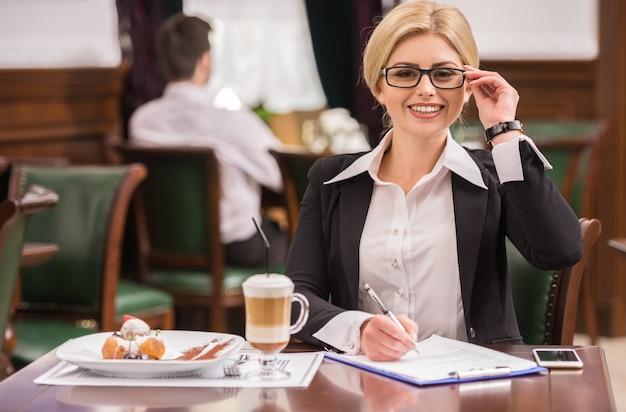 Succesvolle zakenvrouw zittend aan tafel in café.