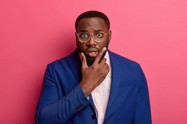Succesvolle zwarte mannelijke ondernemer kijkt geschokt naar de camera, houdt de kin vast, draagt een formeel blauw pak, heeft een sprakeloze blik