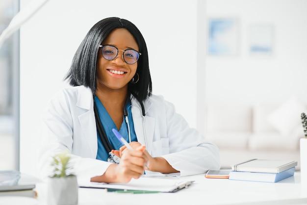 Succesvolle zwarte vrouw arts glimlachend in kantoor