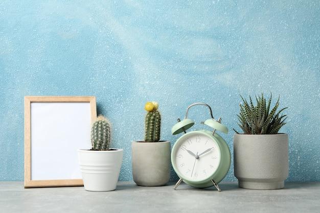 Succulenten, klok en frame tegen blauw oppervlak