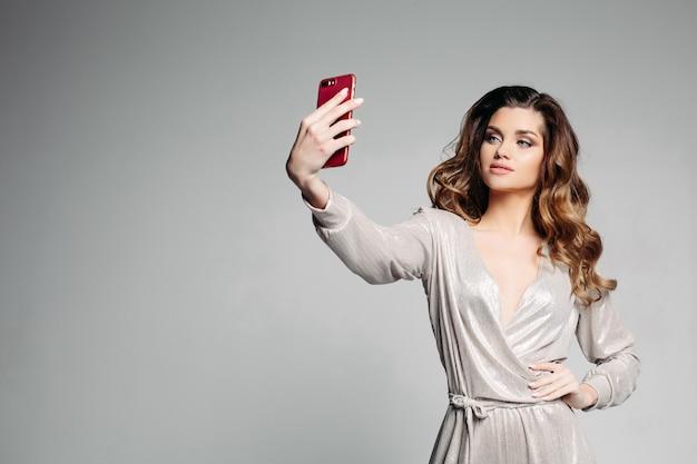 Sudactive vrouwelijk model in zilveren kleding die foto nemen bij smartphone.