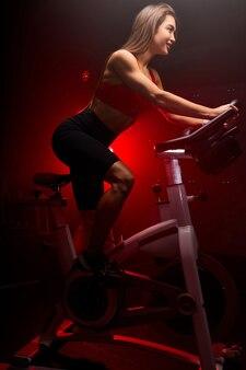 Sude uitzicht op fitness vrouw fietser, zit op de fiets en glimlach, geniet van training. ze traint in de sportschool, fietst op de trainer