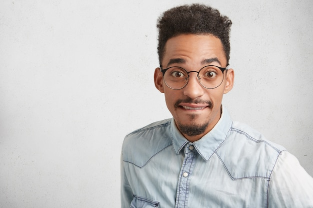 Sudio-opname van verrast knappe mannelijke student met snor, draagt een ronde bril en formele kleding