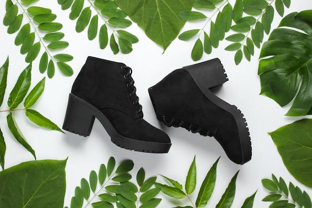 Suède zwarte laarzen op een witte achtergrond met groene bladeren.