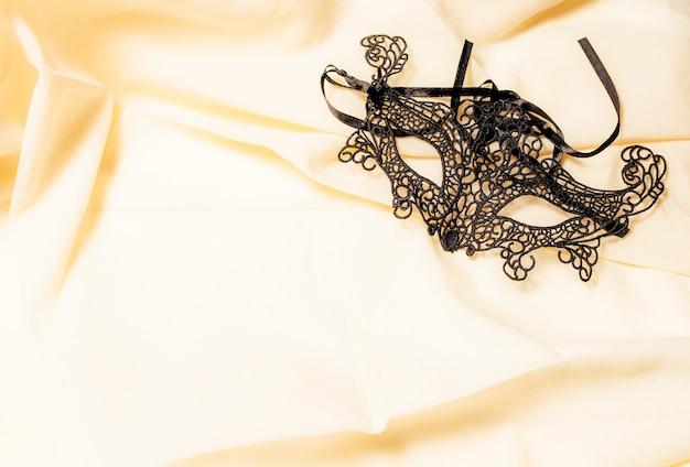 Suggestief zwart venetiaans carnavalmasker alleen op een natuurlijk gekleurde stof. concept mysterie