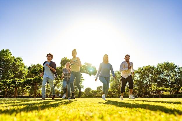Suggestieve lage hoekmening van een groep jonge multiraciale gen-z-vrienden die op groen veld rennen