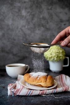 Suiker die over croissant vooraanzicht giet