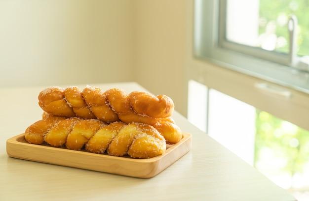 Suiker donut in spiraalvorm op houten plaat wooden