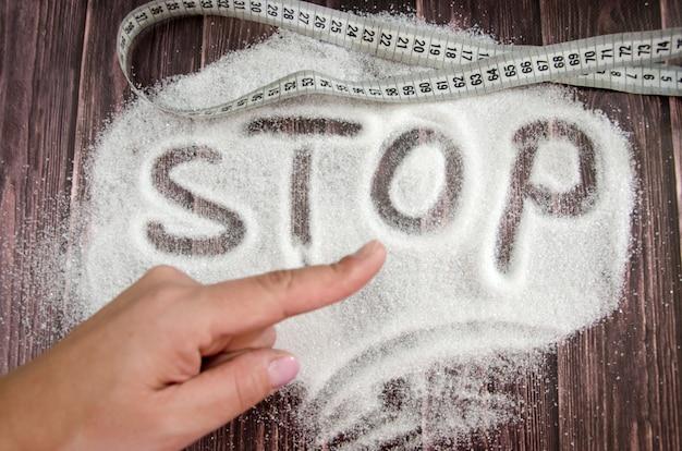 Suiker of diabetes schadeconcept hand wijst naar het woord stop op suiker