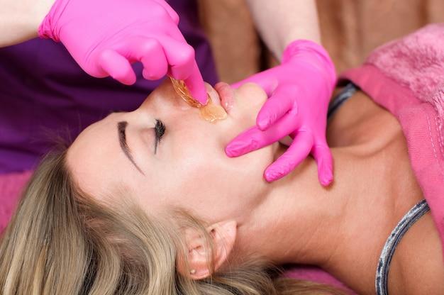 Suiker ontharing uit het lichaam van de vrouw. spa-procedure voor epileren van was. procedure schoonheidsspecialiste vrouw. snor.