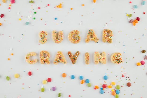 Suiker verlangen inscriptie gemaakt van biscuit letters en versierd met regenboog hagelslag