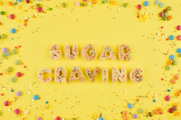 Suiker verlangen inscriptie gemaakt van zoete zelfgemaakte koekjes en kleurrijke snoepjes rond
