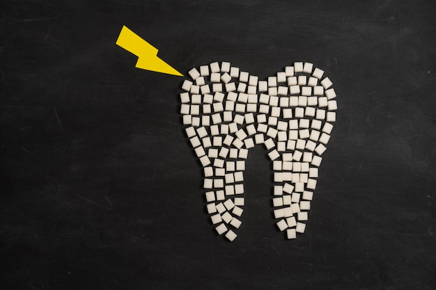 Suiker vernietigen tandglazuur leidt tandbederf witte suikerklontjes vorm tand bruin suiker cariës zwarte achtergrond gezondheidszorg en geneeskunde stomatologie concept zoet voedsel tanden vernietigen