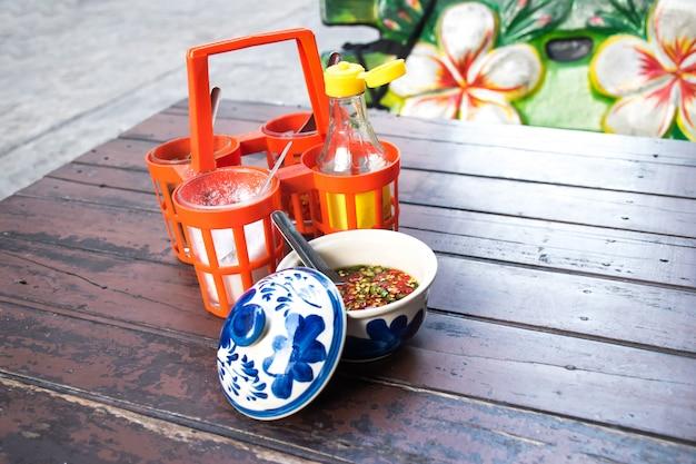 Suiker, vissaus, azijn, cayennepeper, kruiden, thaise noedels op oude houten tafel