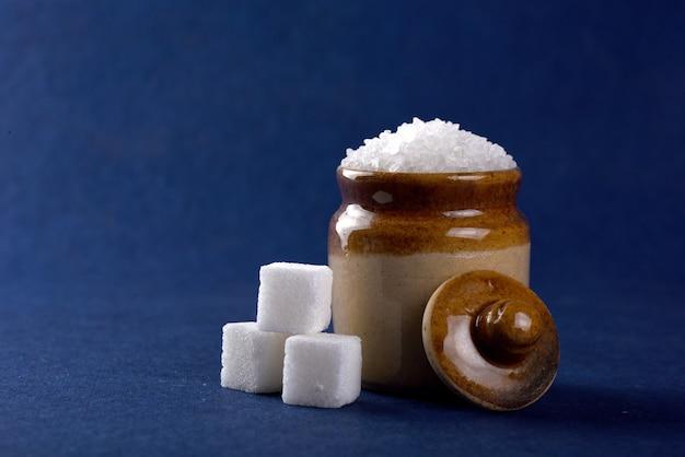 Suiker. witte kristalsuiker en geraffineerde suiker op een blauw