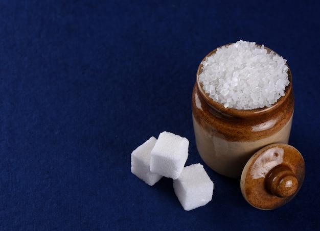 Suiker. witte kristalsuiker en geraffineerde suiker op een blauwe achtergrond