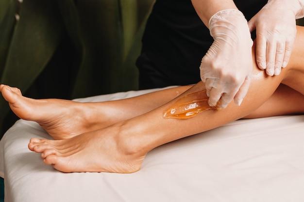 Suikerbehandeling gedaan in de salon tijdens een beenbeschermingssessie