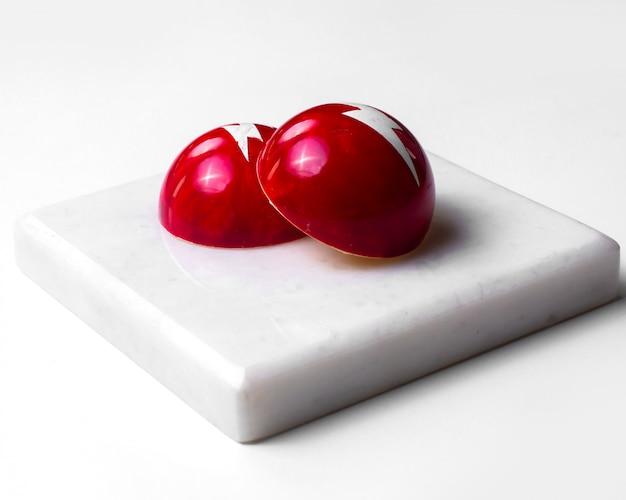 Suikergoed van de zijaanzicht het rode chocolade op witte tribune