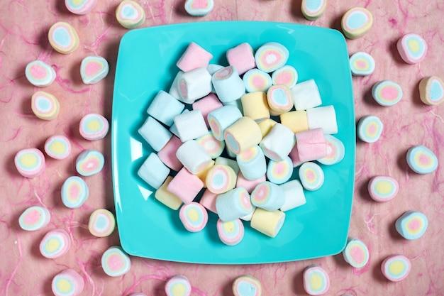 Suikergoed zoete heemst in kleurenschotel op roze achtergrond