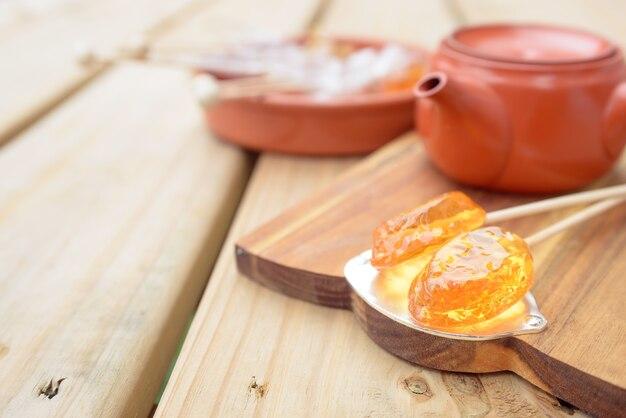 Suikergoedlolly en theepotproductvertoning op houten lijst