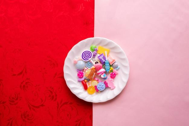 Suikergoedriet op witte plaat met de roze en rode achtergrond van de tafelkleedtextuur.