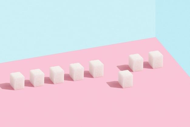 Suikerklontjes op een rij. eentje die opvalt tussen de massa.