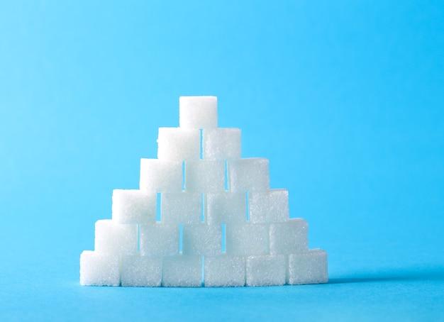 Suikerklontjes piramide over blauwe achtergrond - teveel suiker concept