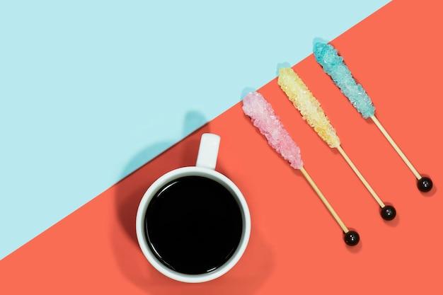Suikerkristal op houten stok met hete koffie op rood en blauw