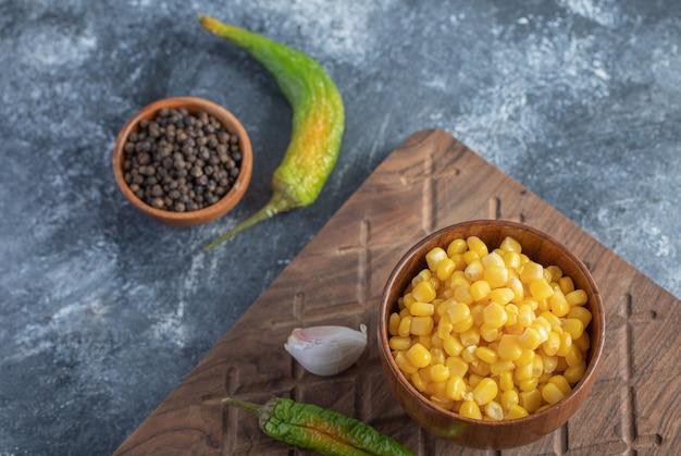 Suikermaïs, knoflook en peper op een houten bord.