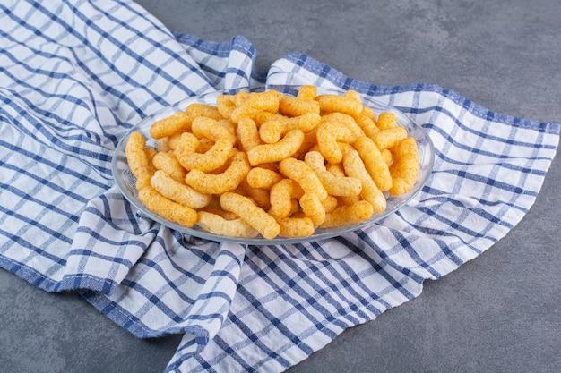 Suikermaïs sticks in een kom op theedoek, op het marmeren oppervlak