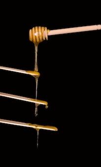 Suikerpasta of schoonheidswas voor het versuikeren stroomt van een houten lepel naar houten spatels