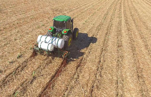 Suikerriet planten door kunstmest en insecticiden toe te passen met tractor