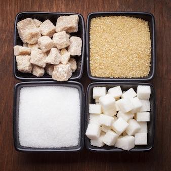 Suikersoorten in zwarte kommen over de houten achtergrond