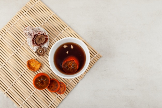 Sujeonggwa - traditionele koreaanse koude vruchtenthee of gekoelde punch op marmeren oppervlak. bovenaanzicht, selectieve aandacht.