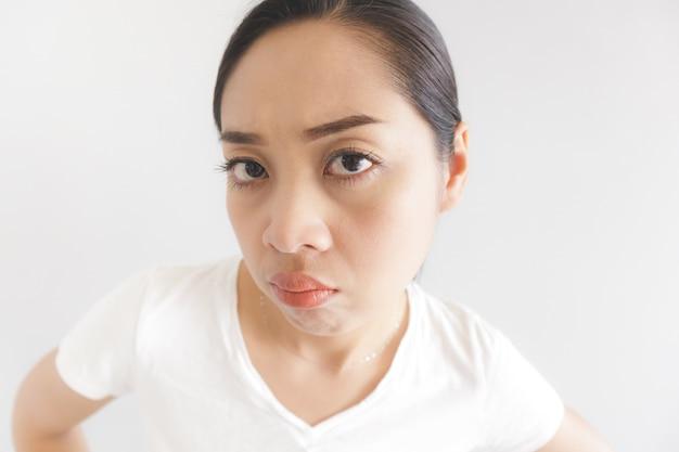 Sulk en knorrige gezichtsuitdrukking van vrouw in witte t-shirt.