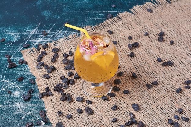 Sultana en citroenen met een kopje drank op blauw.