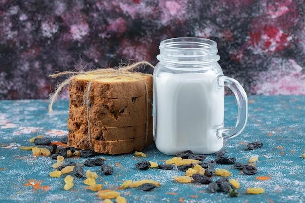 Sultana taart plakjes en een pot melk op blauw.