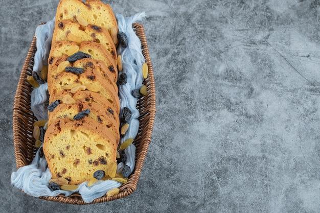 Sultana taart plakjes in een houten bakje op een blauwe handdoek