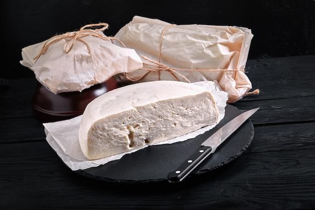 Suluguni georgische kaas gesneden op een houten bord op een donkere achtergrond