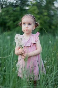 Summer joy is een schattig klein meisje dat een paardenbloem blaast.