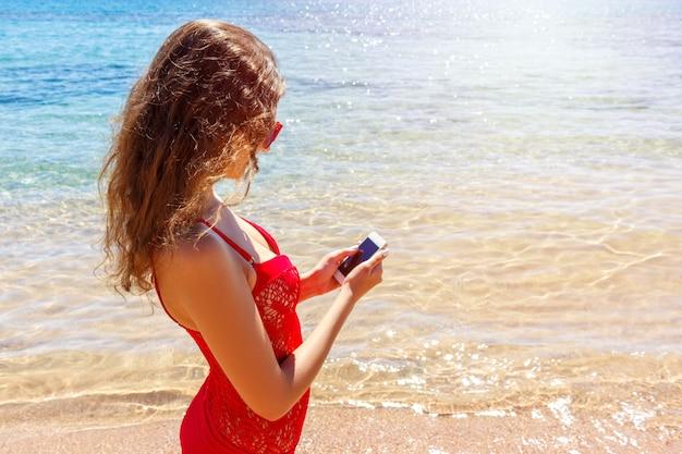 Sunbathermeisje die zwempak dragen die een slimme telefoon met behulp van. zomervakantie op het strand