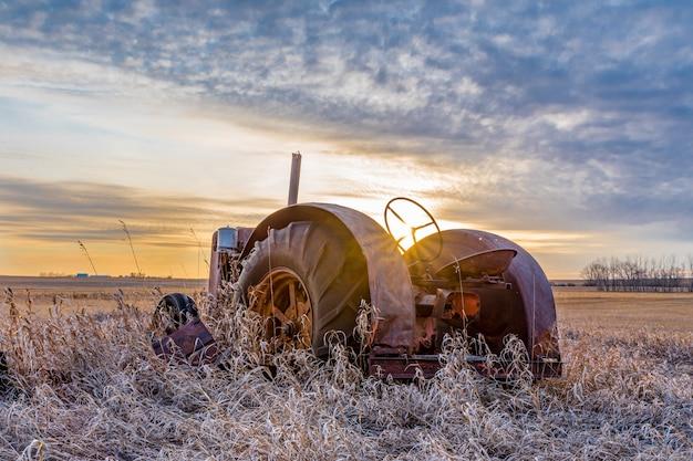 Sunburst bij zonsondergang over een vintage tractor verlaten in hoog gras op de prairies in saskatchewan